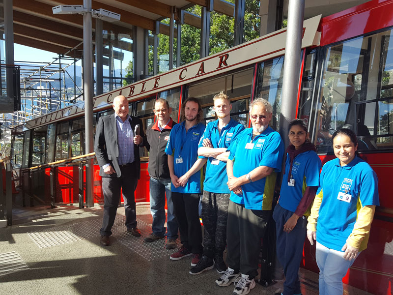 With a good job done for another day, Crest teams take a chance to pose against the background of one of the revamped cable cars. With them are Richard Brodie (CrestClean Wellington Regional Manager), and Matthew Hardy (Passenger Service Manager).