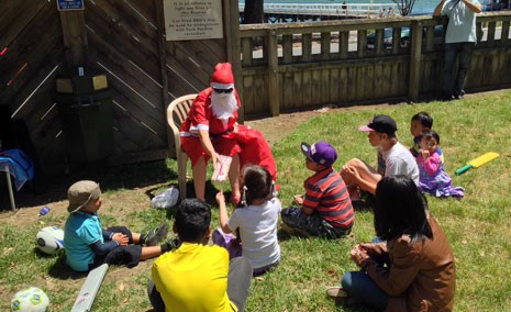 Regional Director Clare Menzies plays Santa with presents for the kids