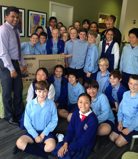 The kids from Sunnyhills Primary School with their new TV, presented by CrestClean's East Auckland Regional Director Viky Narayan.