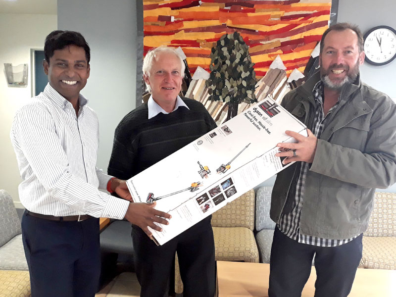 Chris Els receives the vacuum cleaner from Yasa Panagoda. Looking on (centre) is Redwood Primary School Principal John Stackhouse.