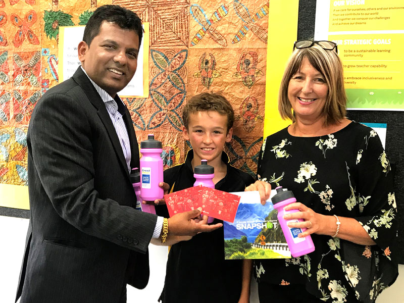 Angela Smith, Principal, receives prizes for the Mauku Fun Run from CrestClean's Viky Narayan. Looking on is pupil Jaxon McMurtrie